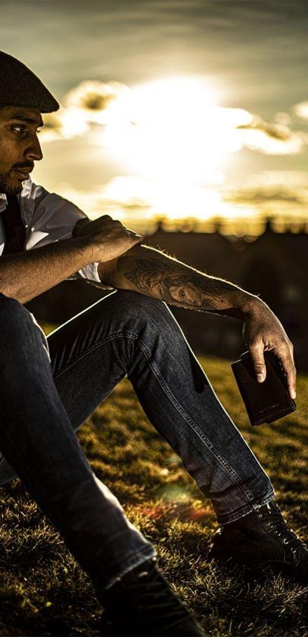 Hombre sostiene cartera de Piel Enrique Escorza en puesta de sol